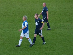 Supporters captain Wayne Wild keeps a close eye on Tugay.